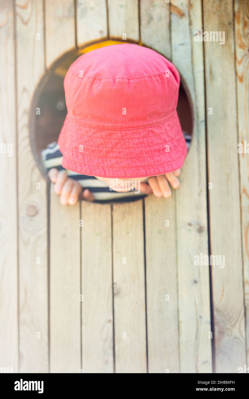 Childhood lifestyle moment. Little girl in read hat looking down from round window in tree house - Stock Image