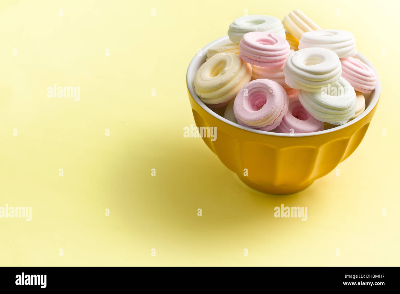 colorful meringues in ceramic bowl on yellow background - Stock Image