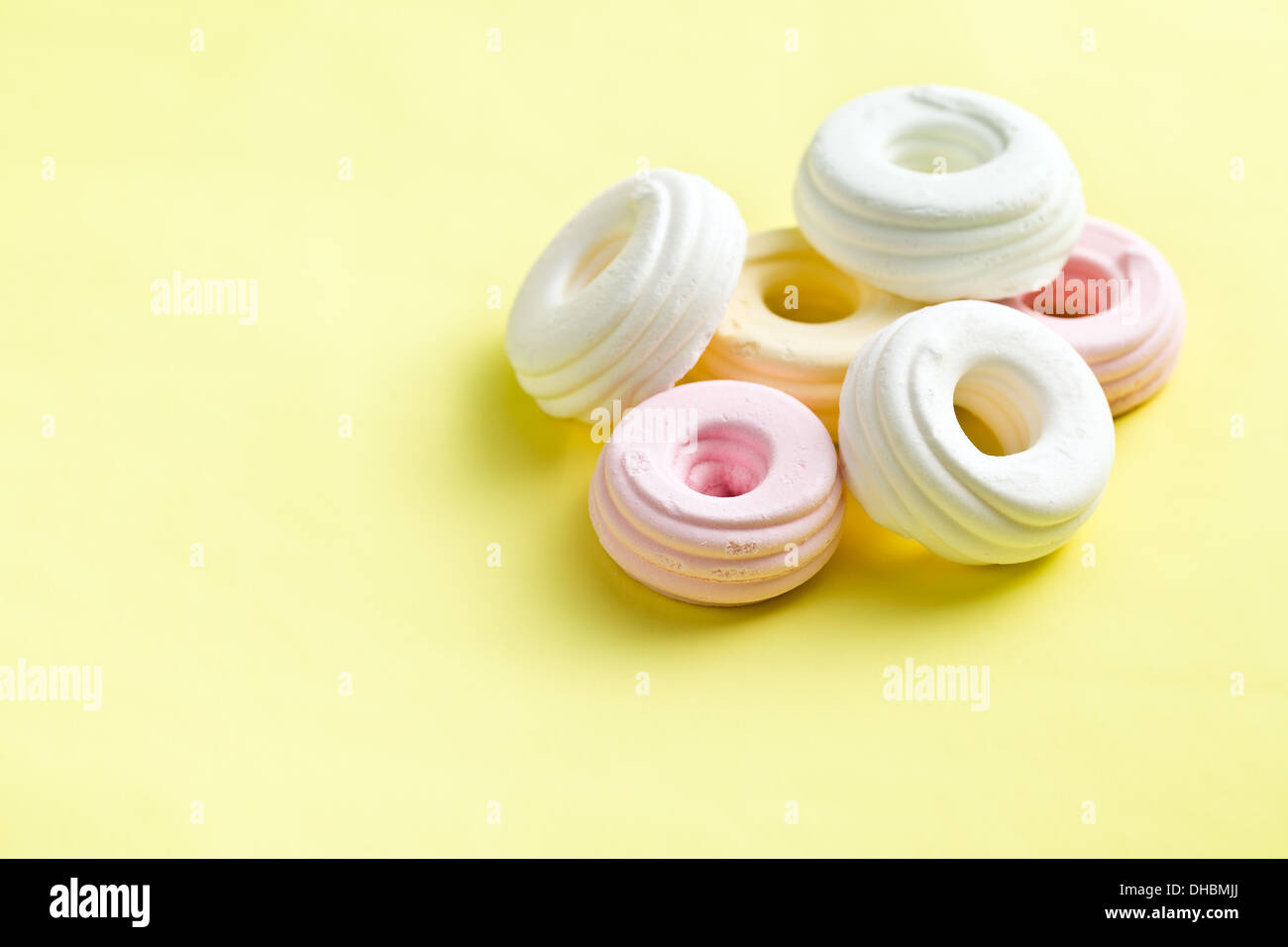 colorful meringues on yellow background - Stock Image