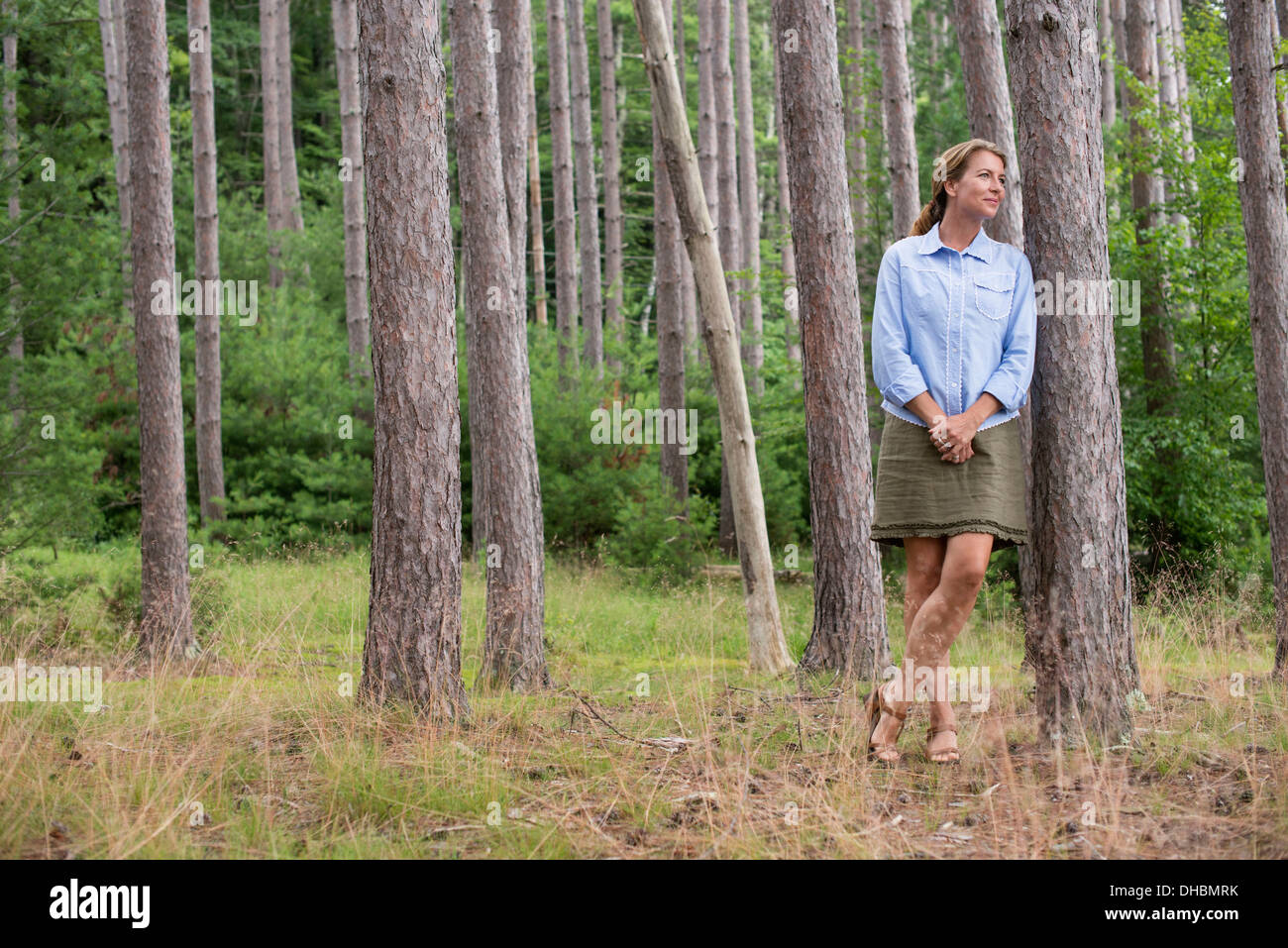 A woman standing among the trees on the shore of a lake in New York state. - Stock Image