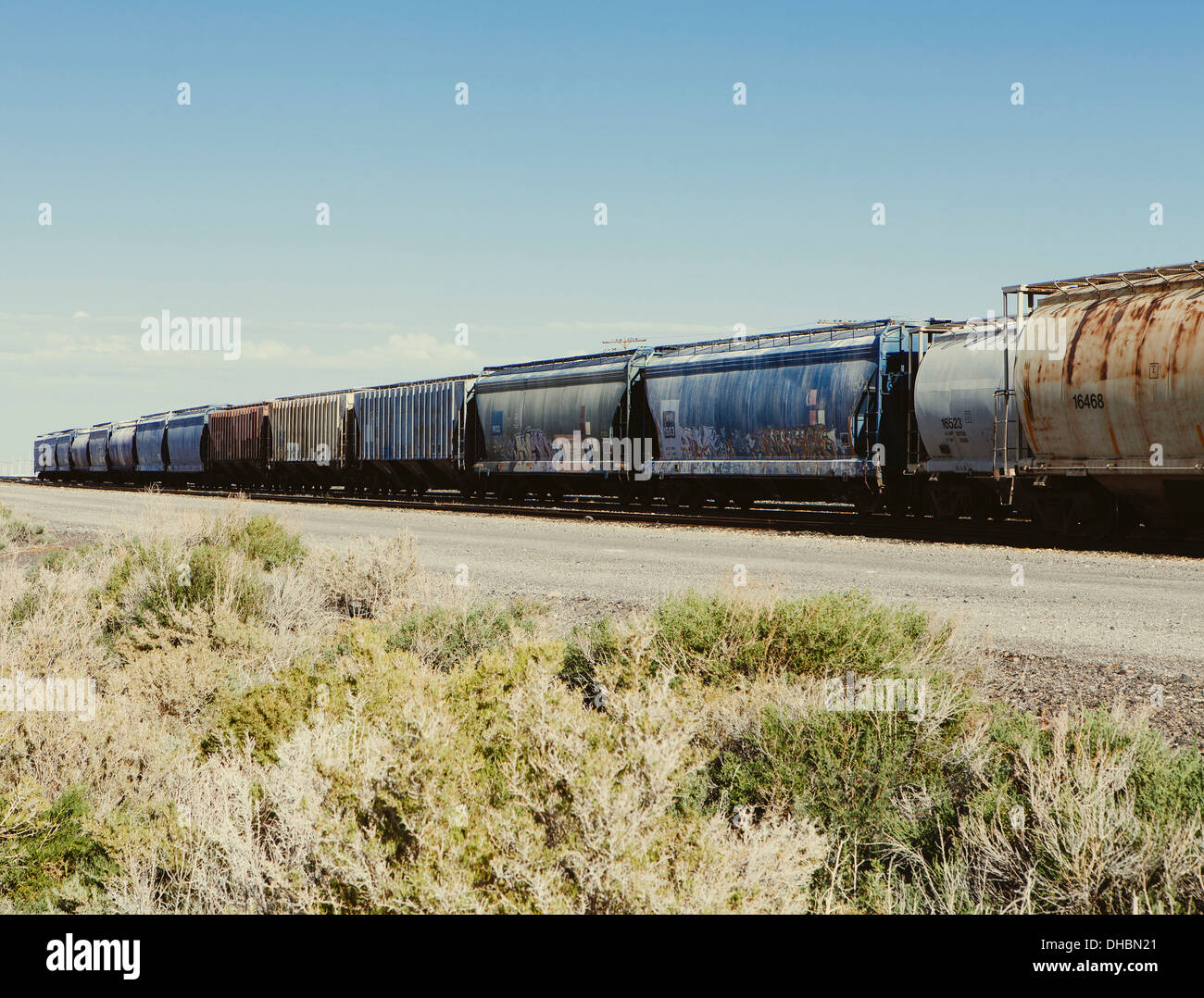 Row of container freight wagons of a freight train crossing the plains near Wendover. Scrubby sage bushes growing - Stock Image