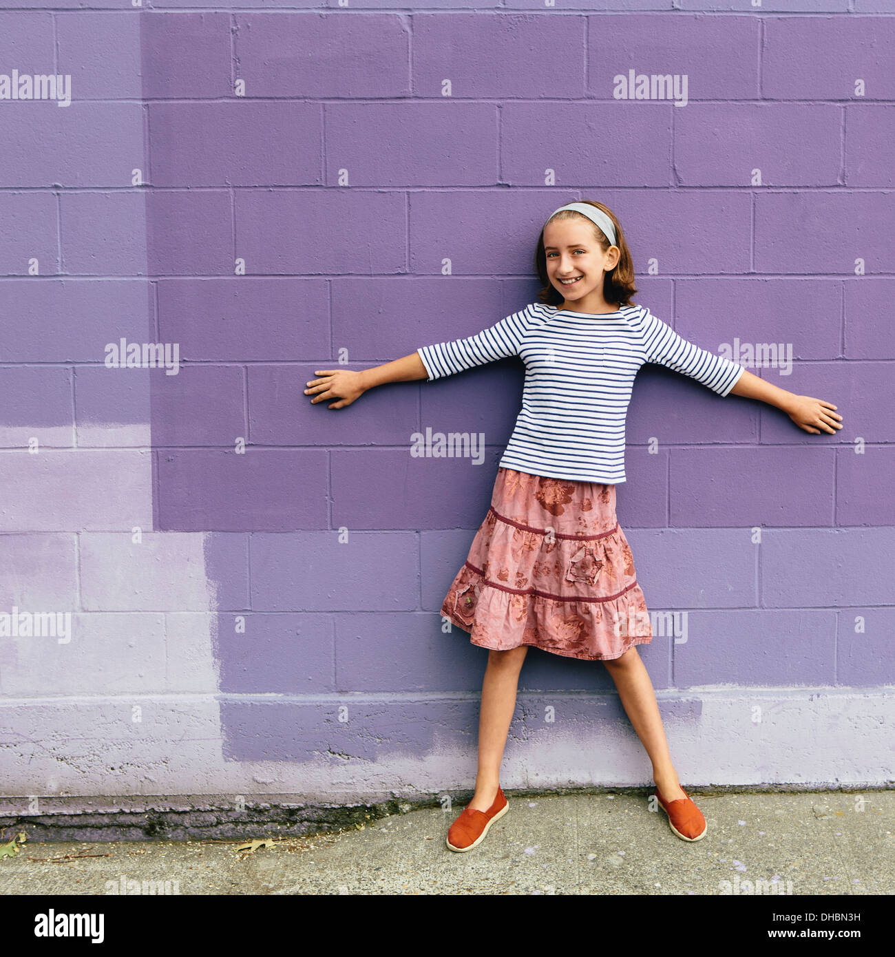 A ten year old girl in a tiered skirt, standing with her arms outstretched, leaning against a wall. - Stock Image