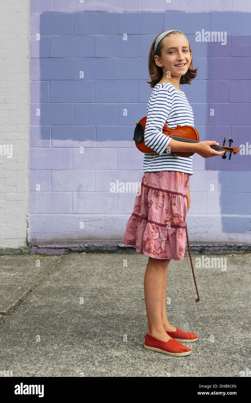 A ten year old girl holding a violin under her arm and a bow in her hand. - Stock Image