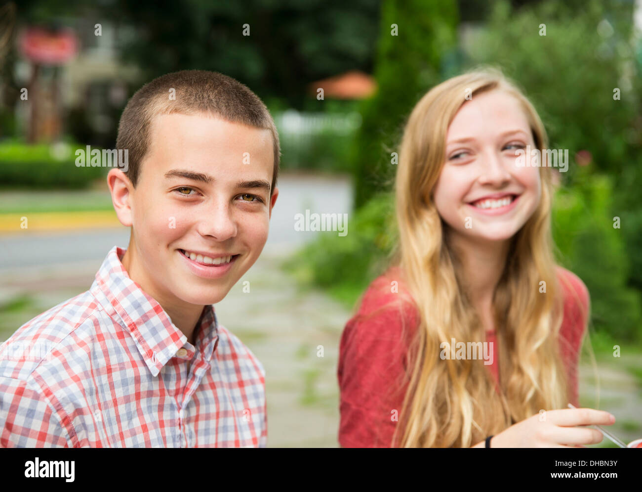 Two young people, boy and girl sitting side by side laughing. - Stock Image