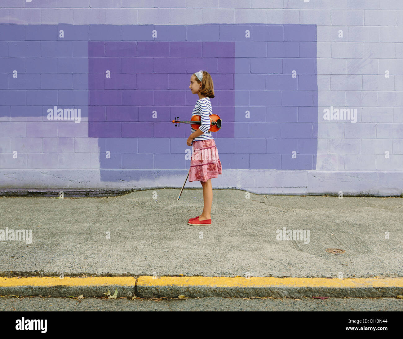 A ten year old girl holding a violin under her arm and a bow in her hand. Against a purple background. - Stock Image