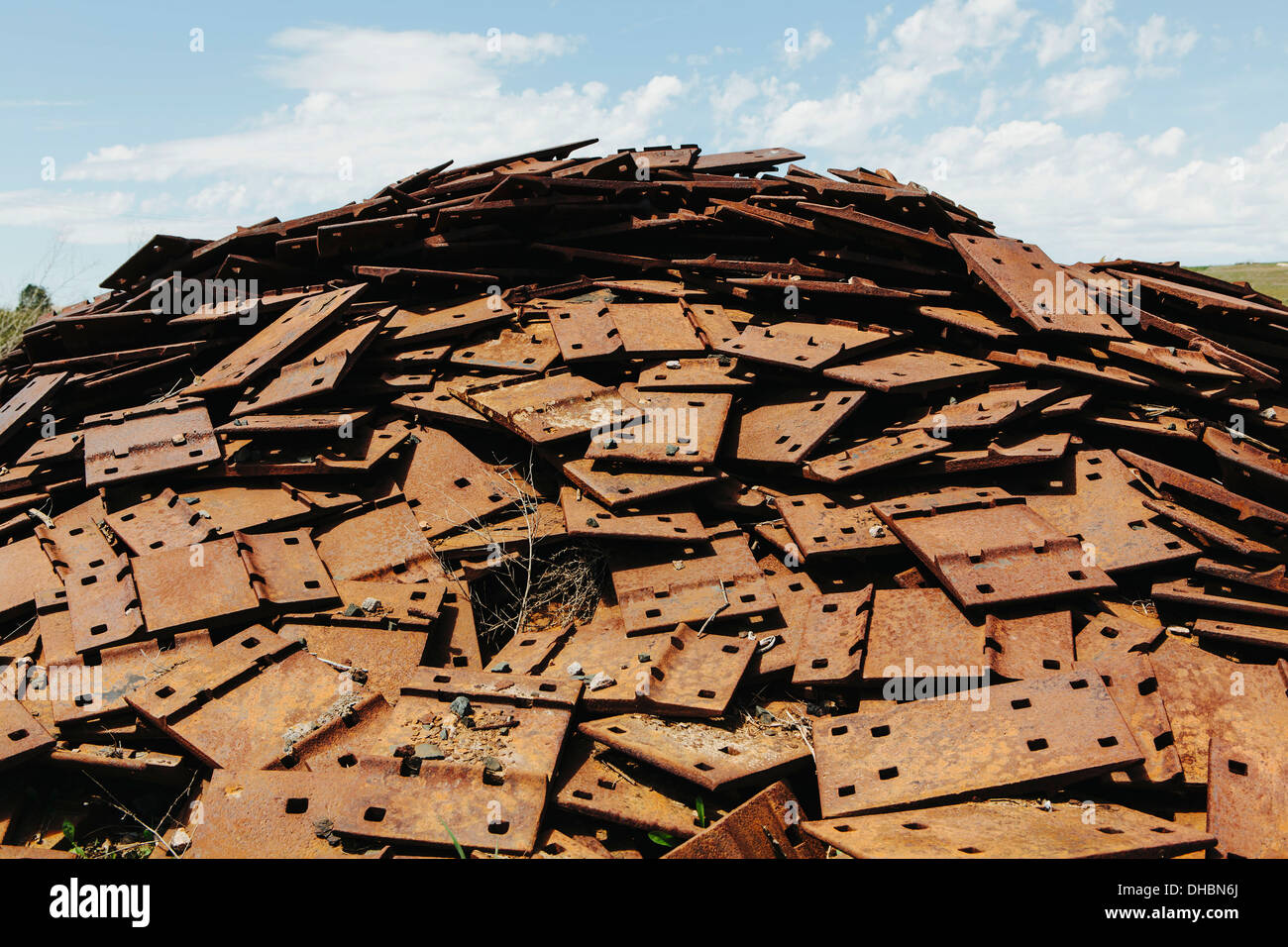 A large pile of rusty plates, used for railroad construction. Discarded or piled up for recycling. - Stock Image