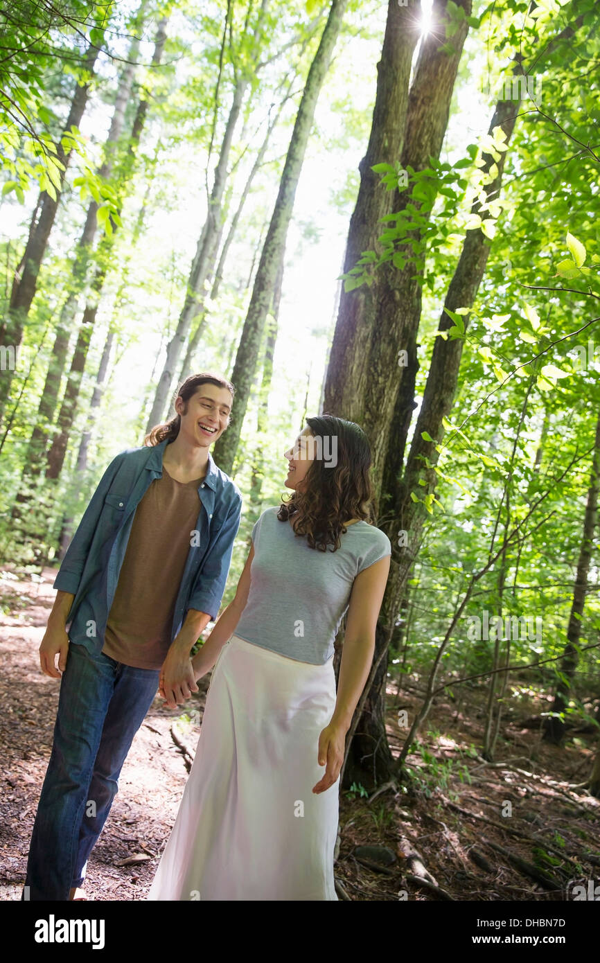 Two people, a young woman and man, walking side by side in the woods. - Stock Image