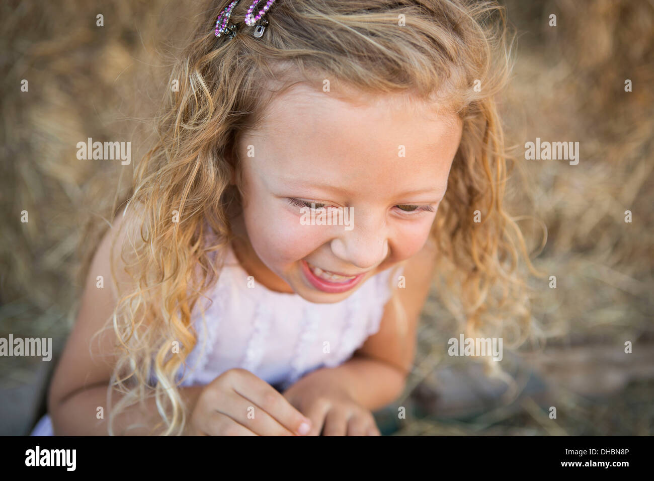A young girl in a barn laughing. - Stock Image
