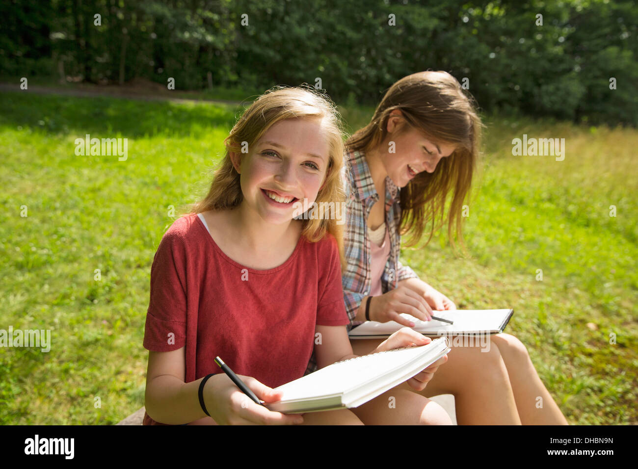 Two young girls sitting outside on the grass, with sketch pads and pencils. - Stock Image
