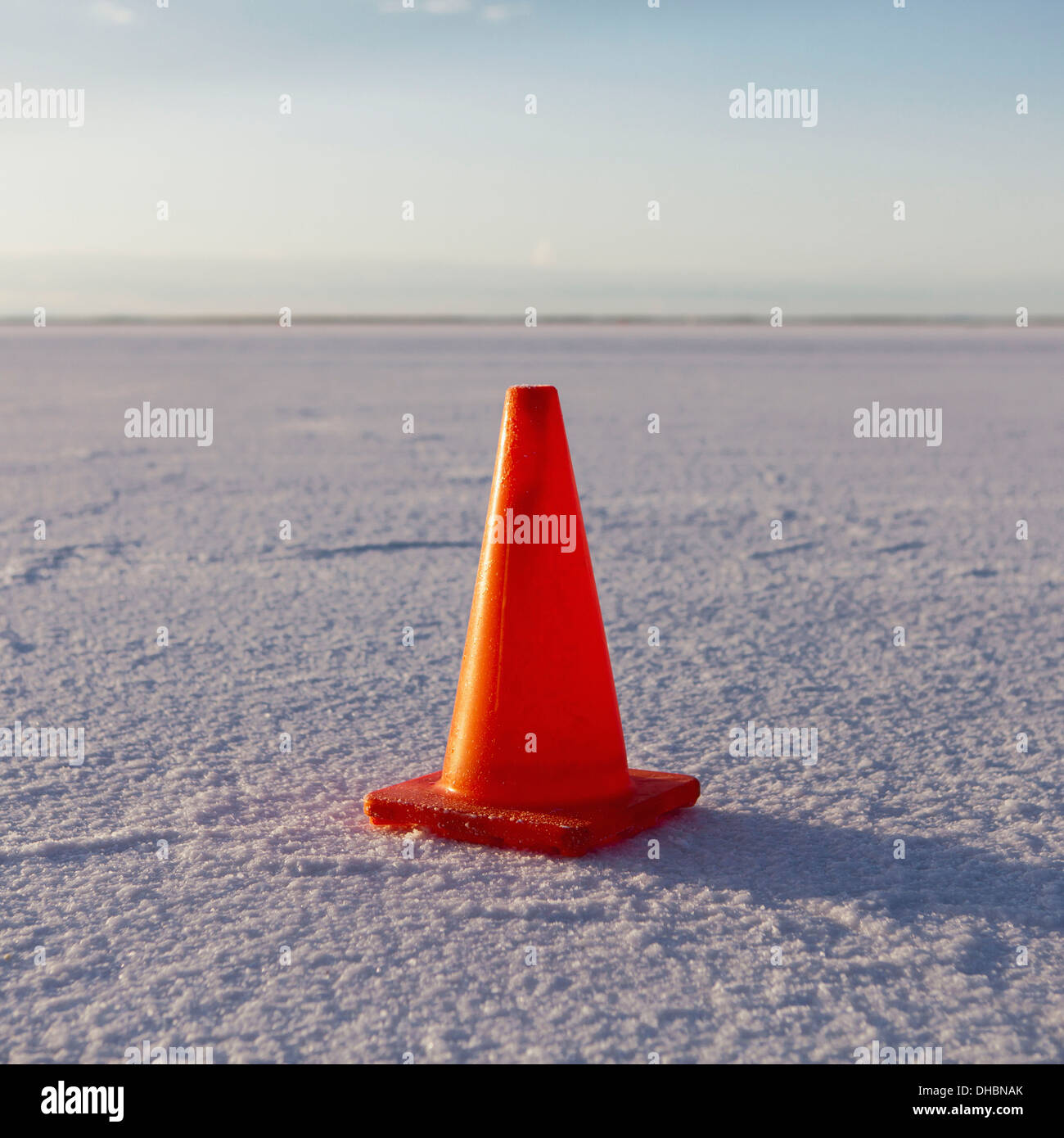 A solitary traffic cone on the white reflective mineral dusted surface of the Bonneville Salt Flats in the early - Stock Image