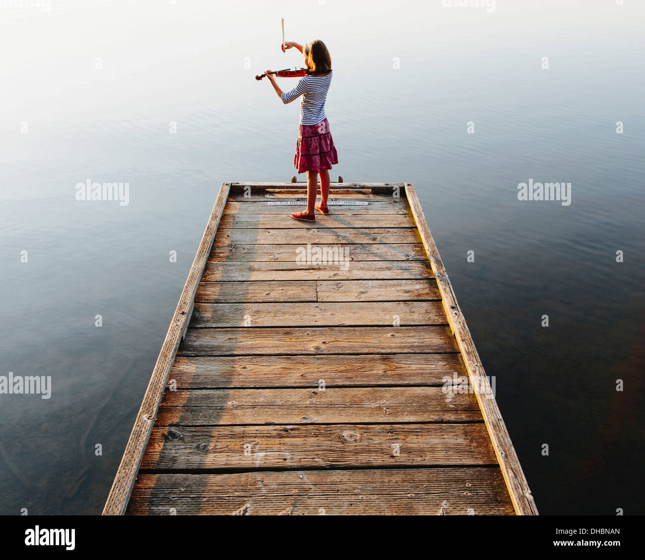 A ten year old girl playing the violin at dawn on a wooden dock. - Stock Image