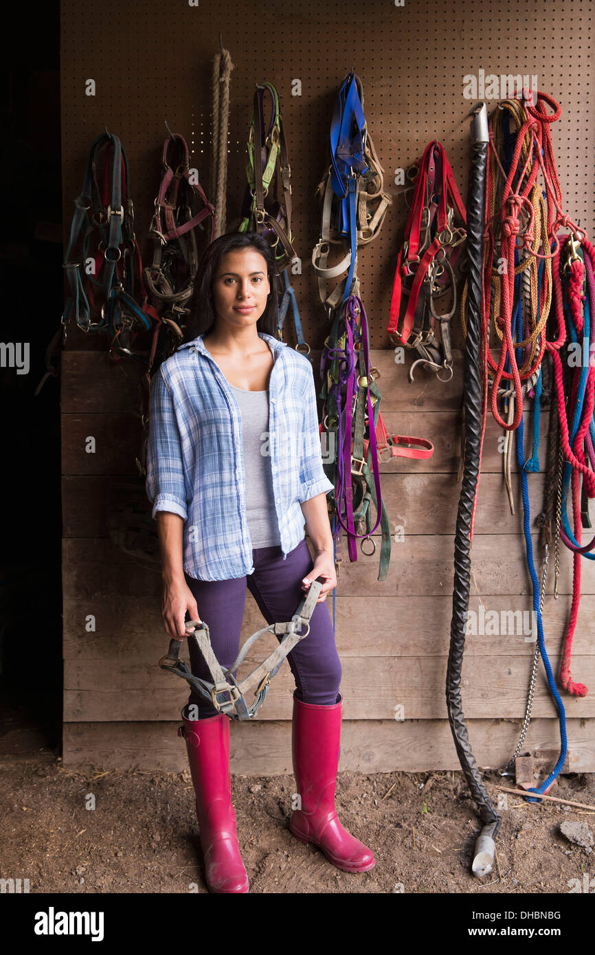 An organic farm in the Catskills. A person standing in a tack room in a stable. - Stock Image