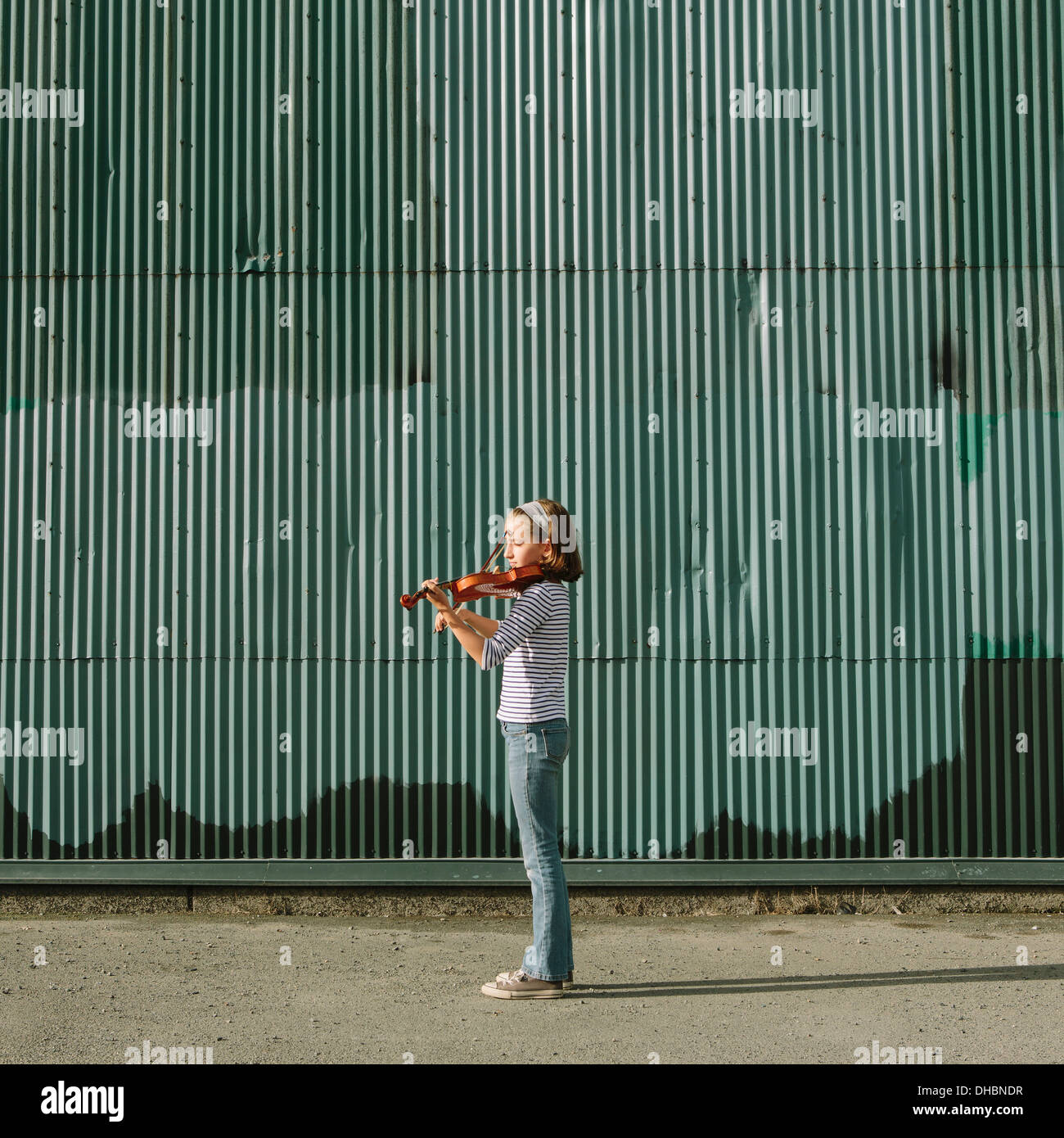 A ten year old girl playing the violin on an urban street. - Stock Image