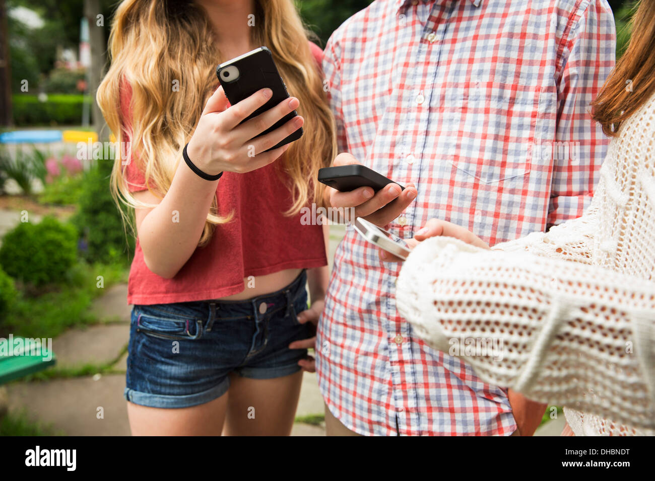 Two friends, a boy and girl looking at their phones. - Stock Image