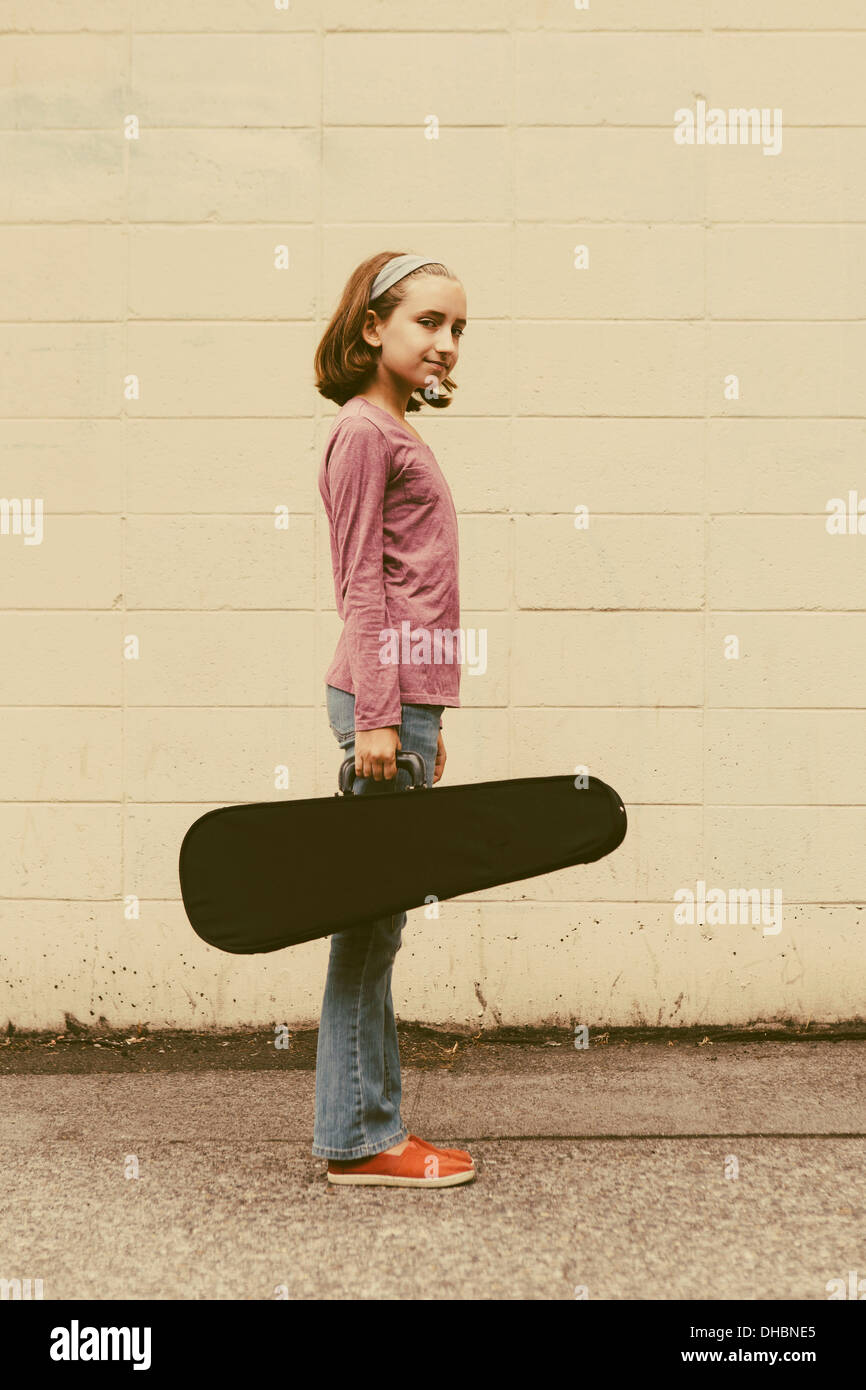 A ten year old girl carrying a violin in a case on an urban street. - Stock Image