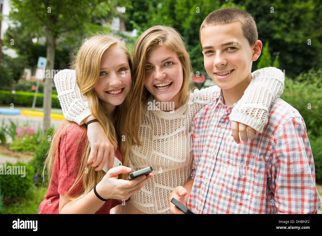 Three young people, two girls and a boy, posing and taking selfy photographs. - Stock Image