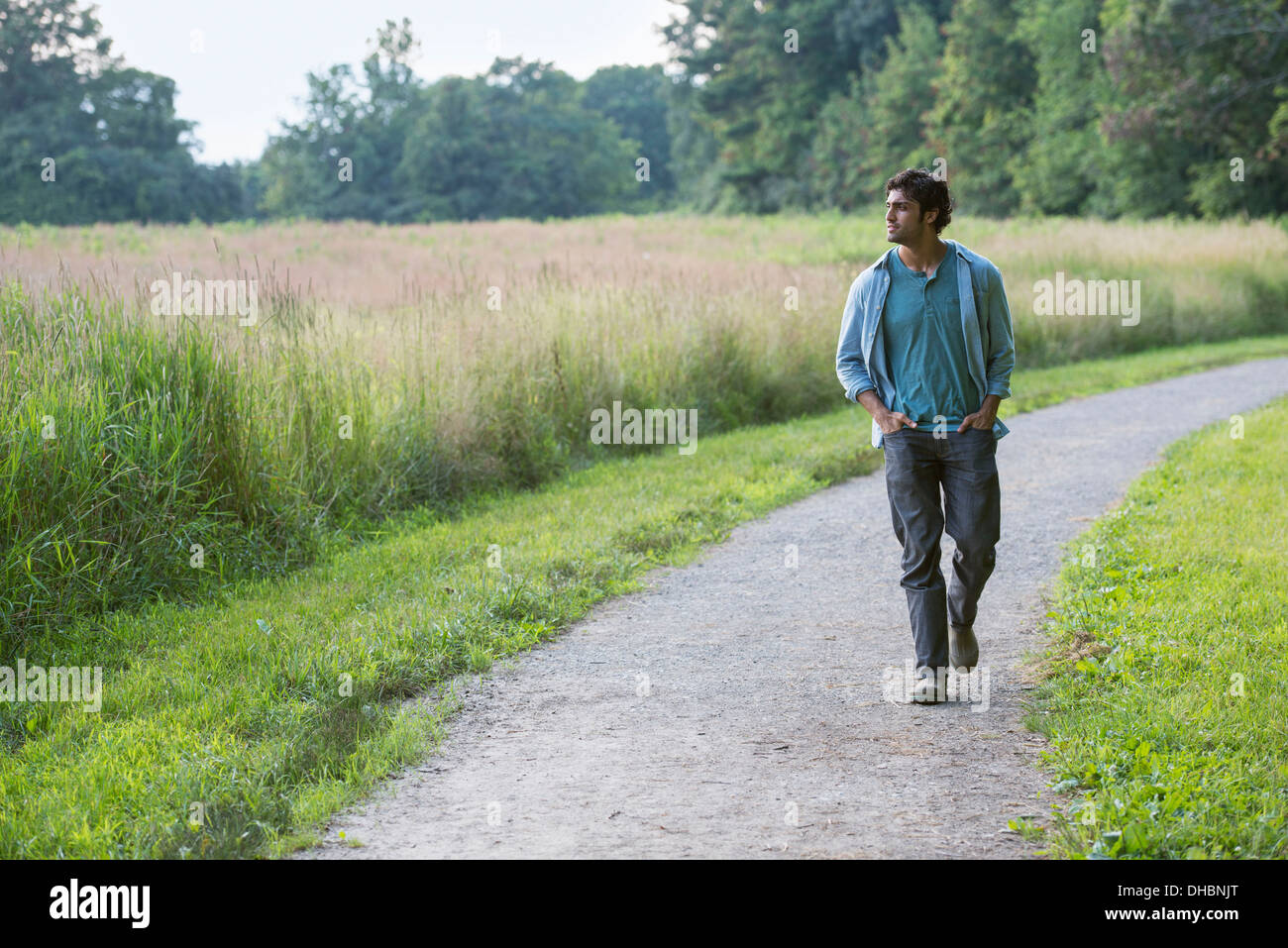 A young man walking down a path with his hands in his pockets. - Stock Image