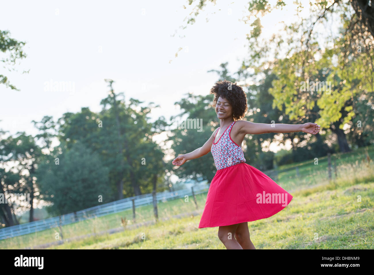 A woman in a red skirt, whirling around in the open air, with her arms outstretched. - Stock Image