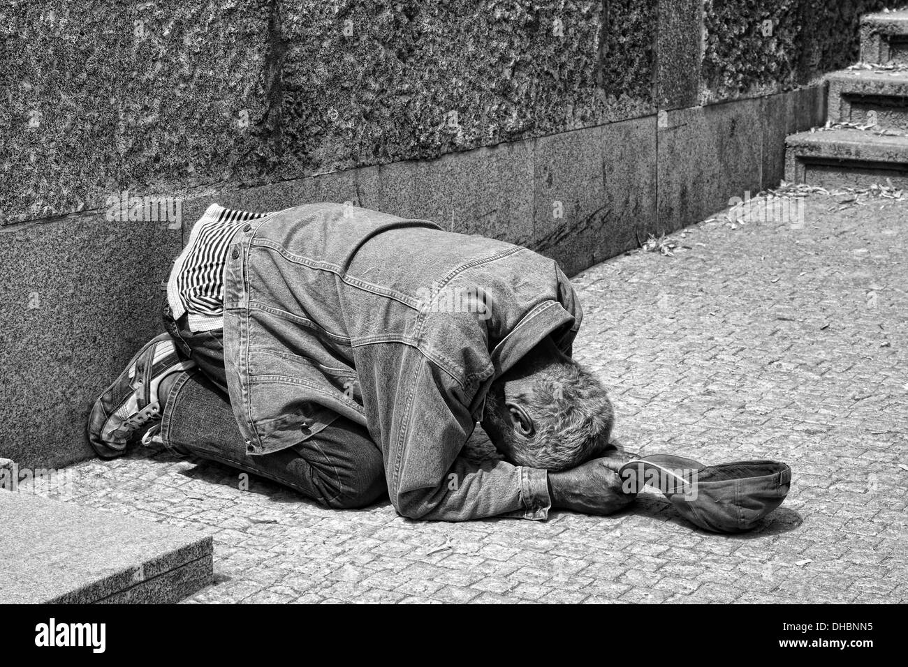 One of the many homeless in Prague, Europe lying on the street next to the river, begging tourists for money. - Stock Image
