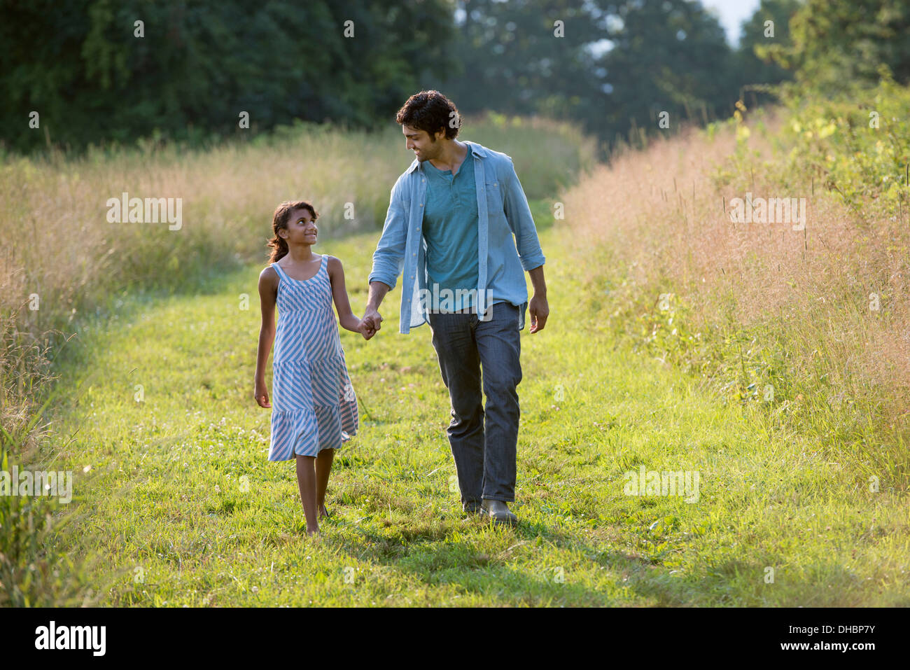 A man and a young girl walking down a mown path in the long grass holding hands. - Stock Image