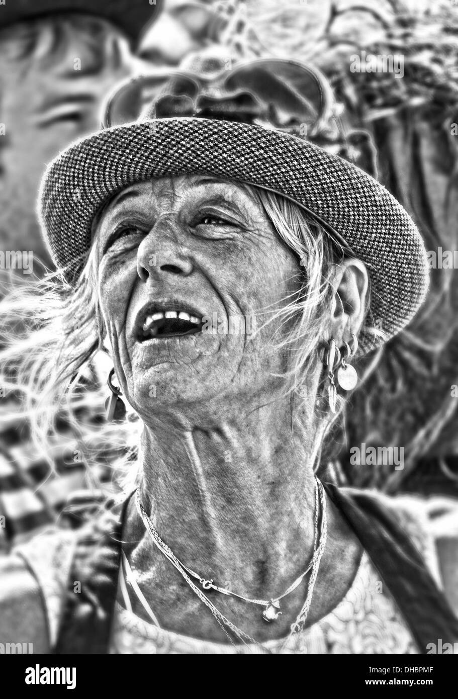 A black and white reportage style portrait of a white European female age 40-50 at a rock, music festival - Stock Image