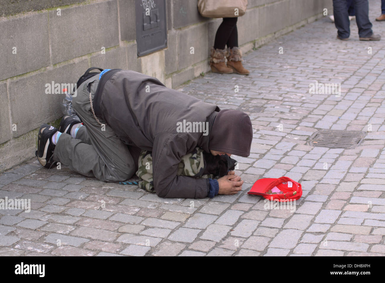 Beggar on The Charles Bridge in Prague, with his Dog, begging tourists for money. - Stock Image