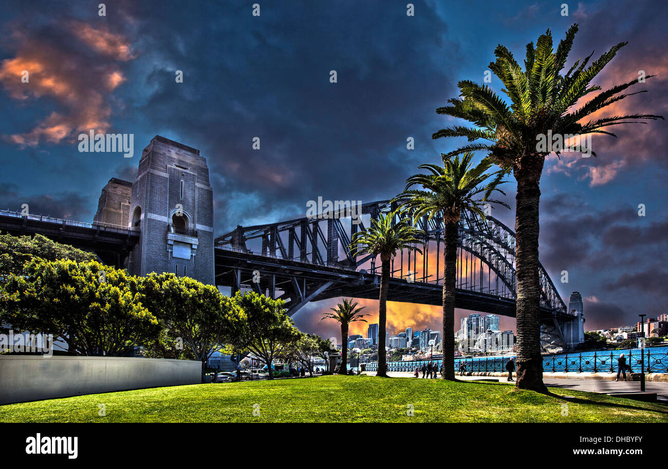 A black and white and color photograph of Sydney harbor bridge in Australia against a dramatic sky - Stock Image