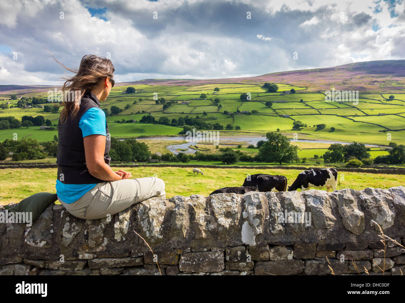 Female hiker sitting on wall near Reeth village in The Yorkshire Dales National Park, England, UK - Stock Image