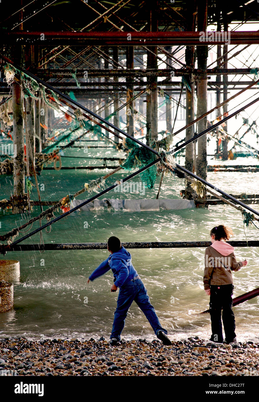 flotsam and jetsam under Brighton pier with kids throwing stones into the sea - Stock Image