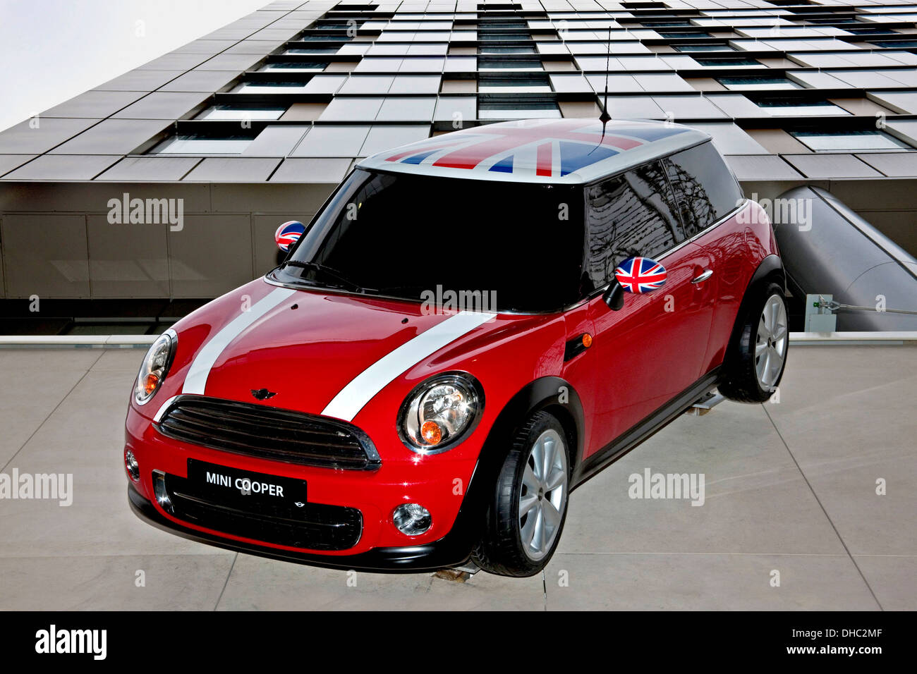 Mini cooper car with union flag on roof and side mirrors, hung on wall at Westlake shopping center Stratford London - Stock Image