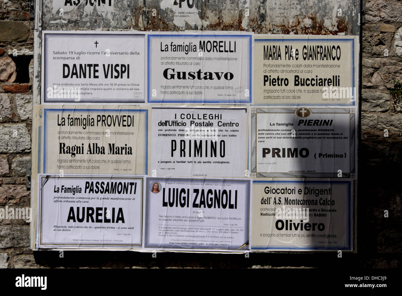 Death announcements on a wall in Gubbio, Italy - Stock Image