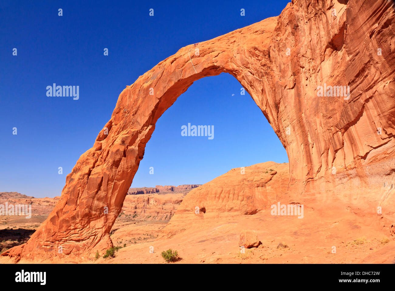 Corona Arch and the moon in a clear blue sky near Moab, Utah - Stock Image