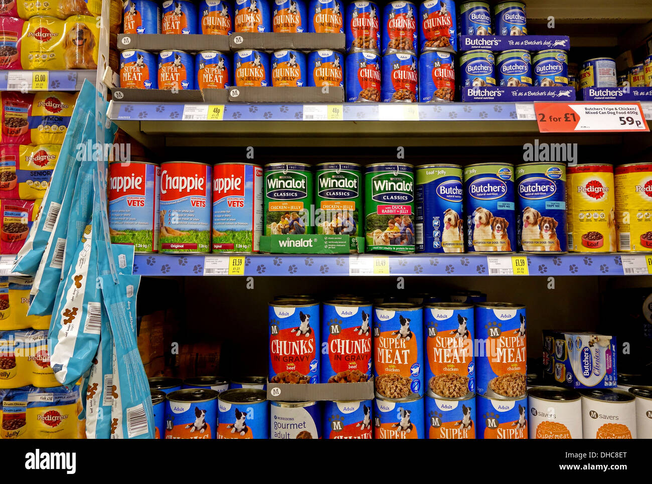 tins of dog food in a supermarket - Stock Image