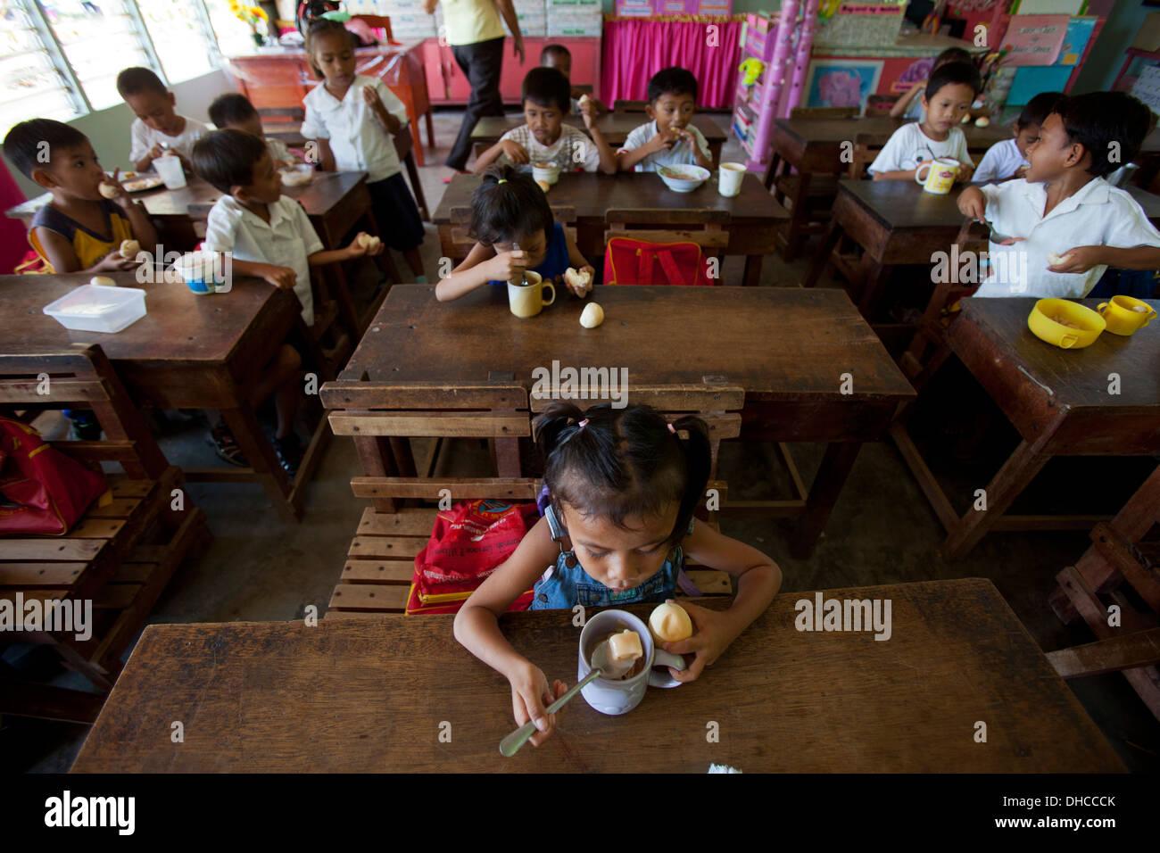 Children enjoy a free lunch during a feeding program event at Wasig Elementary School in Wasig, Oriental Mindoro, Stock Photo