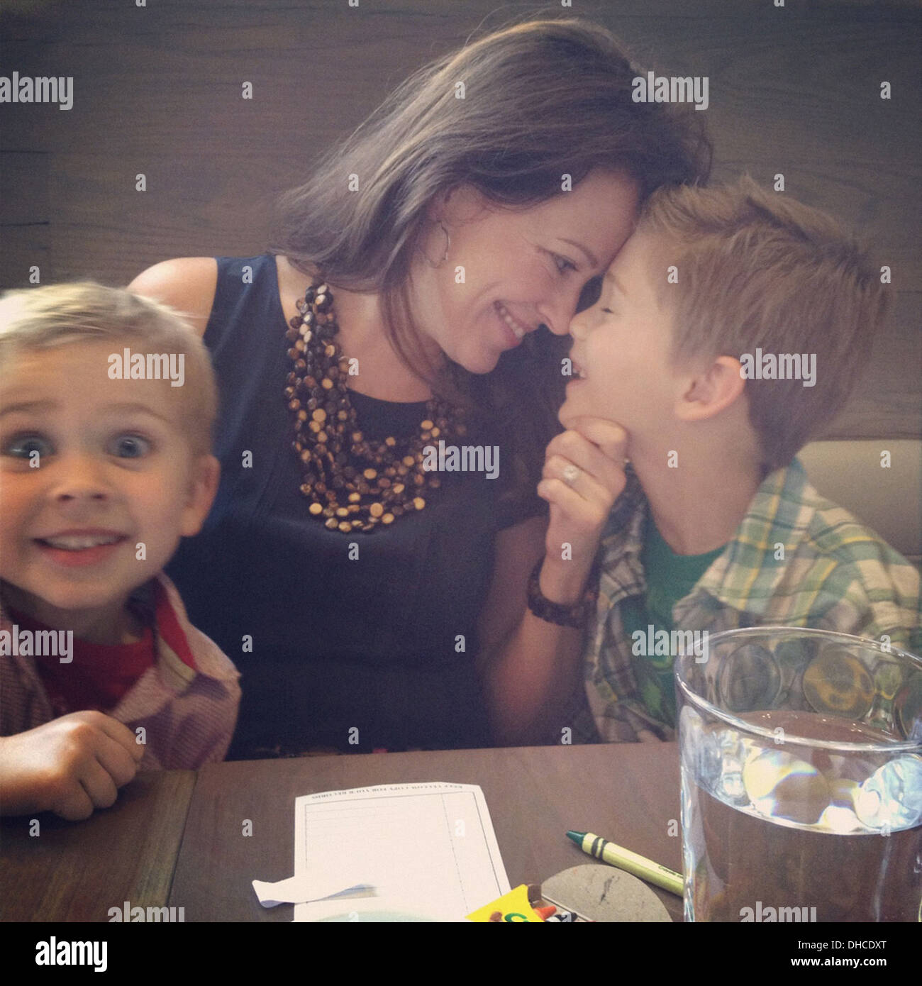 Happy Mother and Two Sons at Restaurant Table - Stock Image