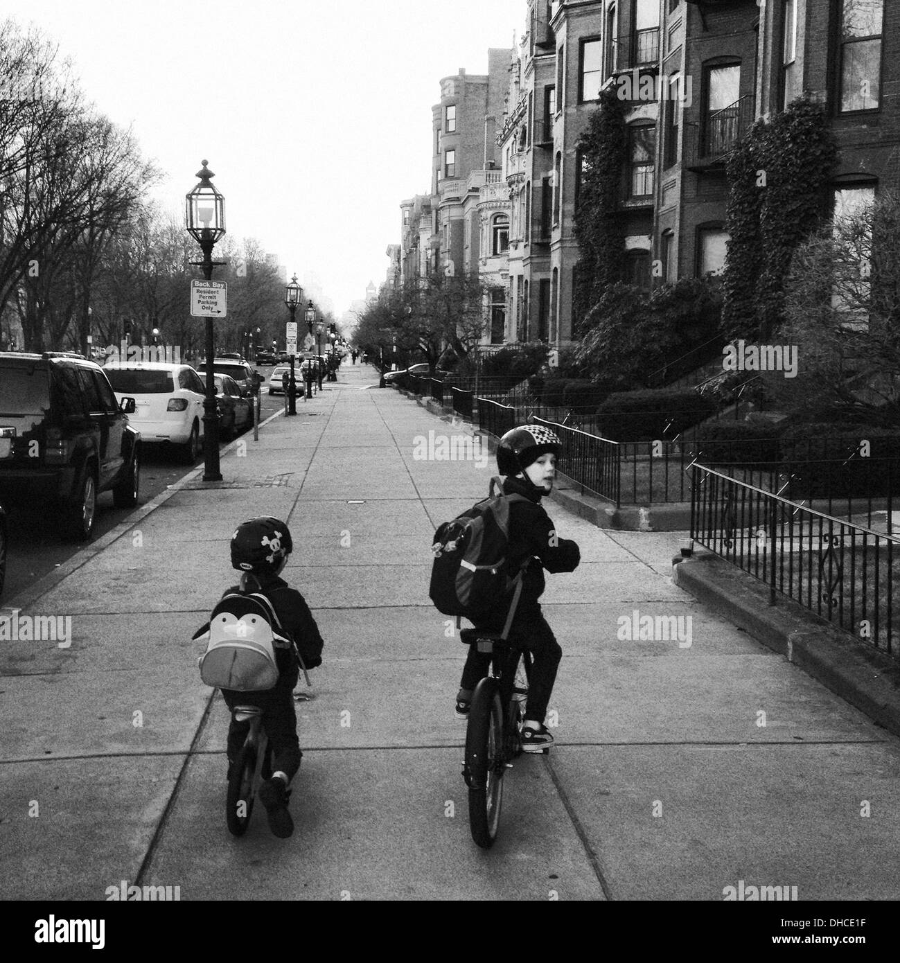 Two Boys Riding Bicycles on Urban Sidewalk, Rear View - Stock Image