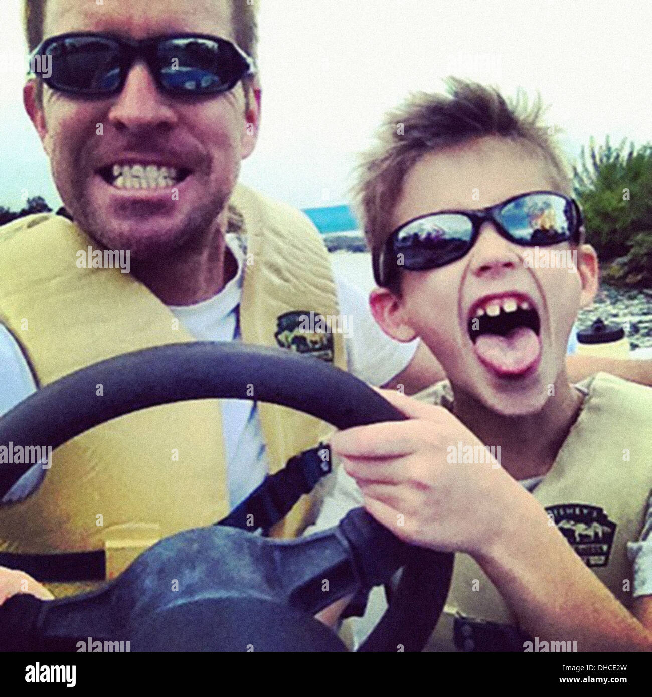 Father and Son Having Fun Behind Wheel of Boat, Close Up - Stock Image