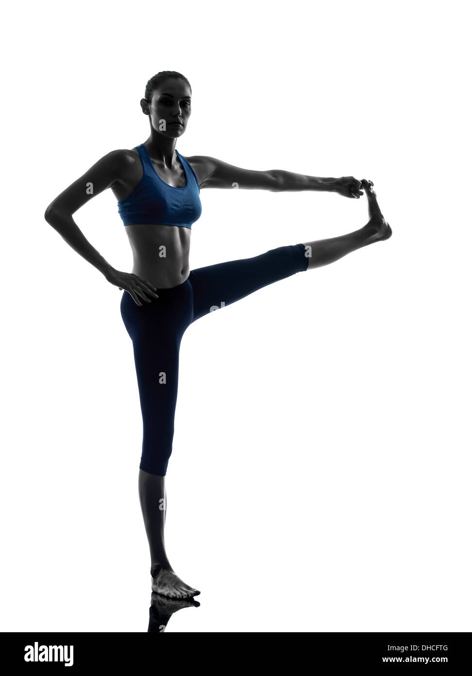 woman exercising yoga Hasta Padangusthasana  Hand To Big Toe silhouette shadow white background - Stock Image
