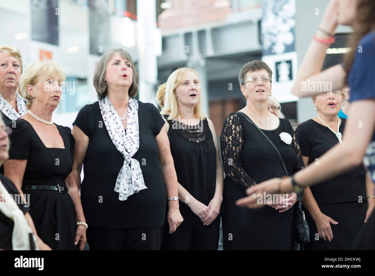 Members of a mixed Choir singing at the National Waterfront Museum in Swansea. - Stock Image