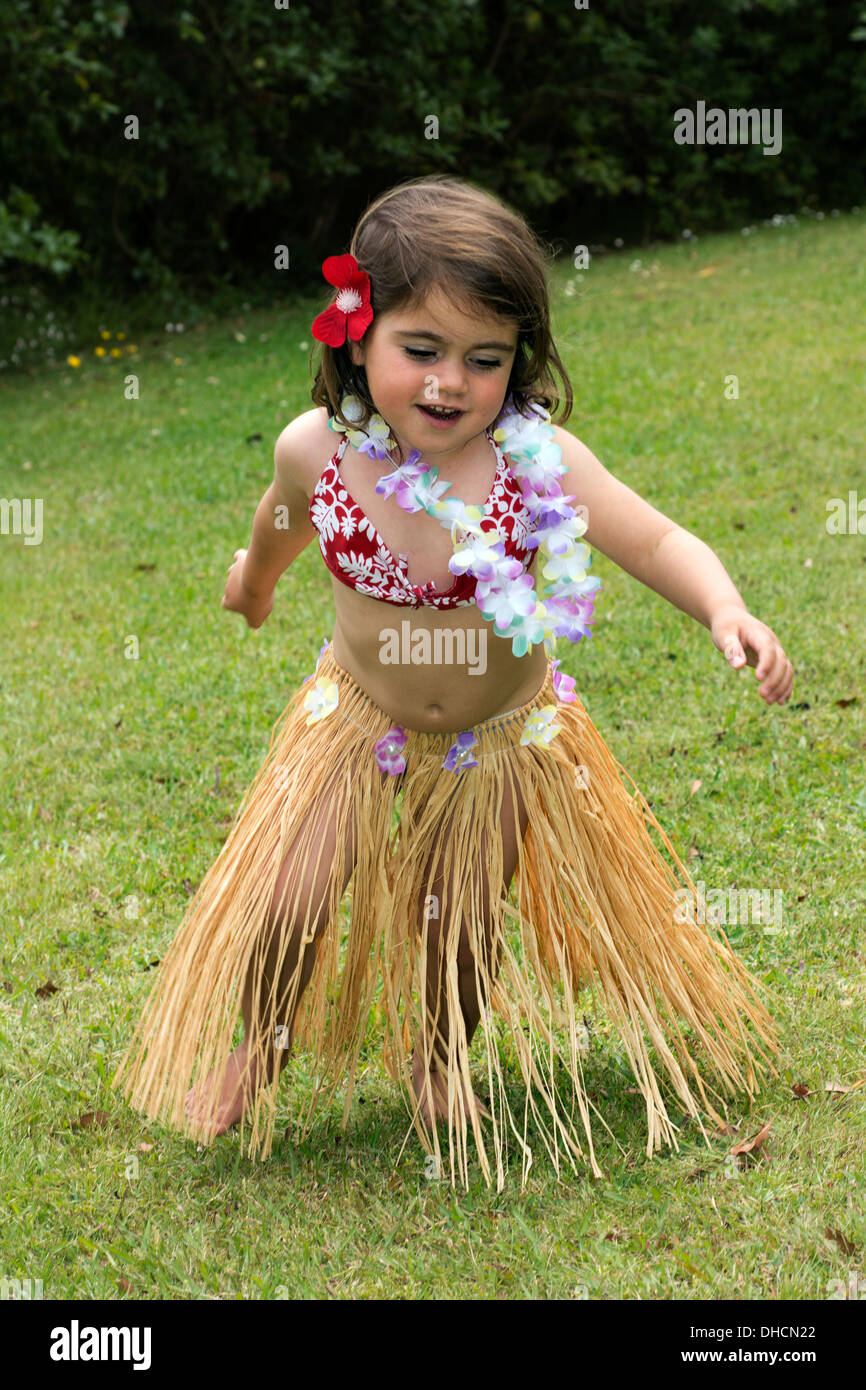 Little girl with Hawaiian Costume of hula dancer, Hula girl dancing outdoor in the garden over green grass barefoot. - Stock Image