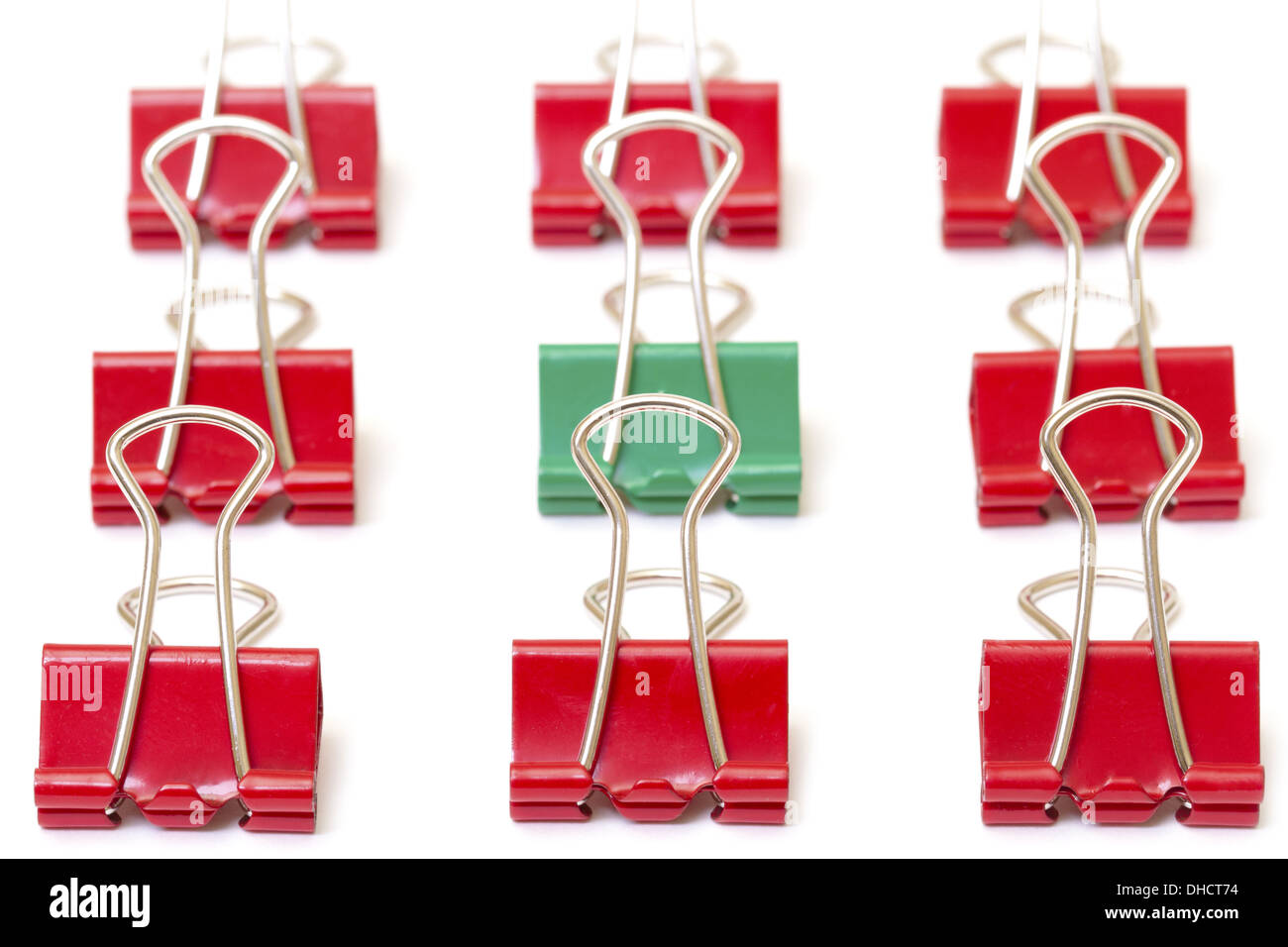 Green paper clip among red - Stock Image