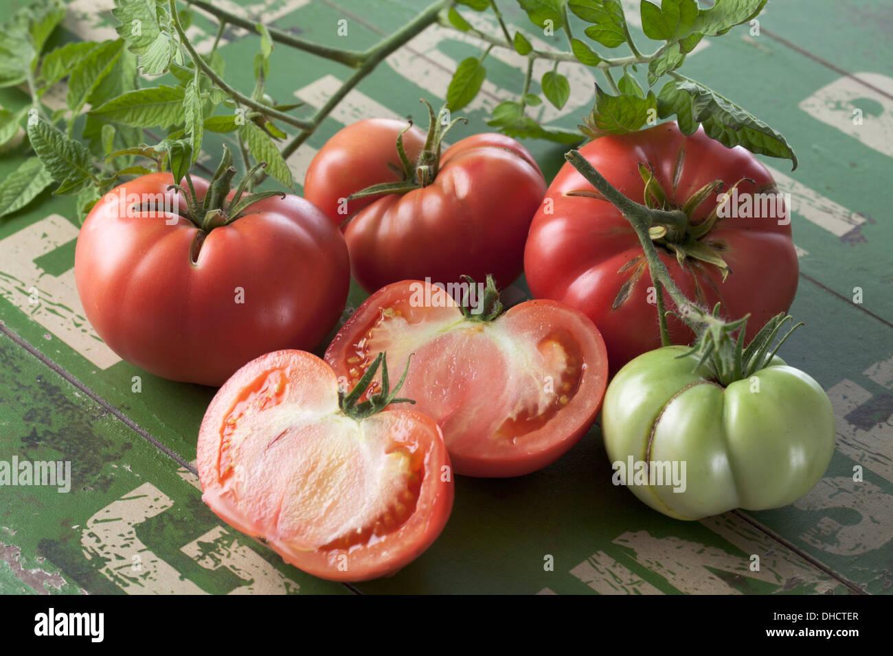 Whole and sliced Silesian raspberry tomatoes (Solanum lycopersicum), studio shot Stock Photo