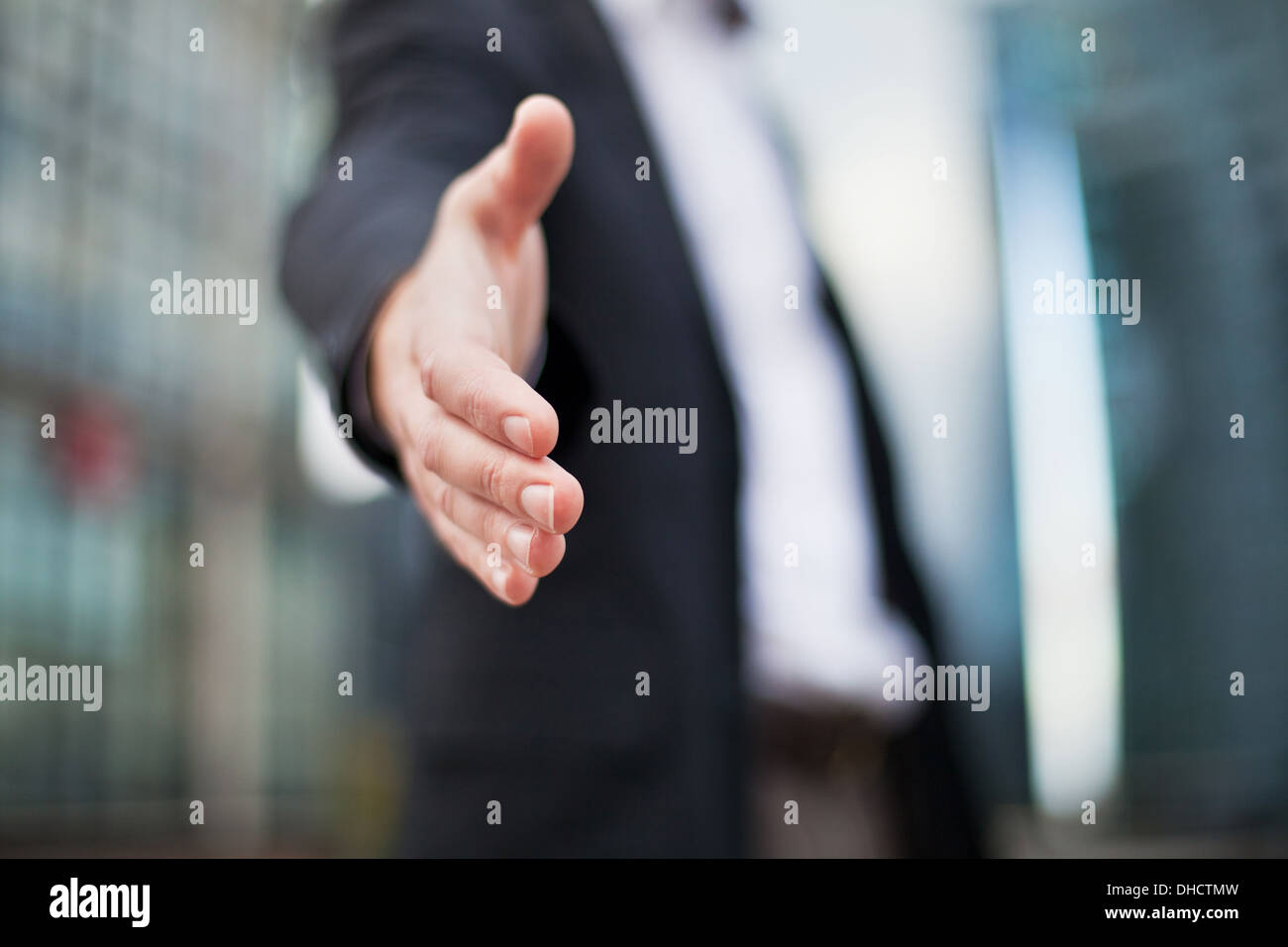Businessman offering for handshake on office buildings background - Stock Image