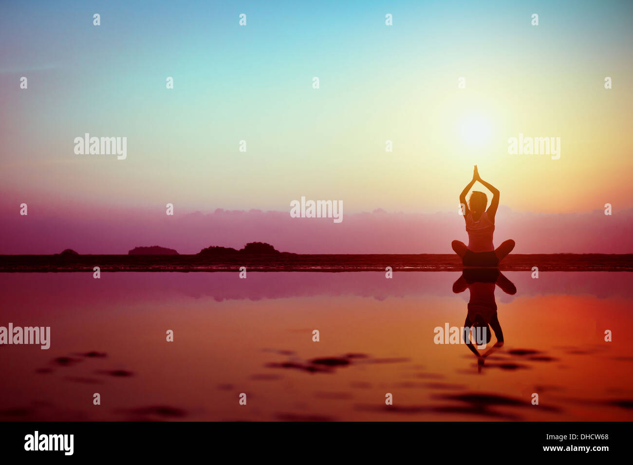 Silhouette of young woman practicing yoga on the beach at sunset - Stock Image
