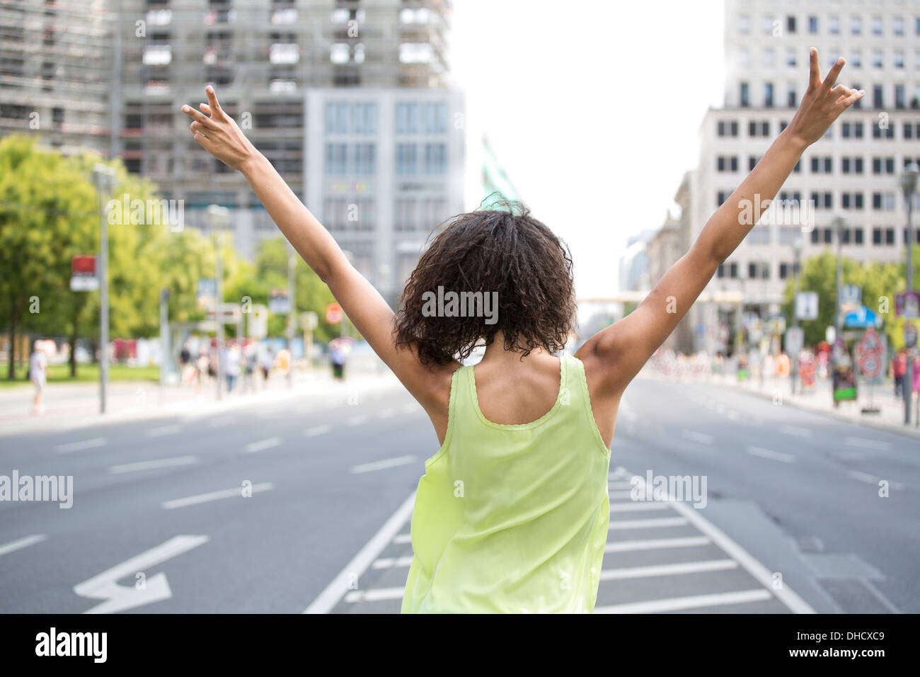Germany, Berlin, Young women in the city, making victory sign, rear view - Stock Image