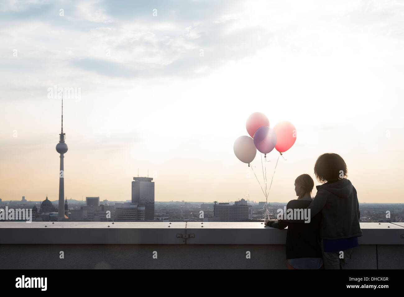 Germany, Berlin, Young women on rooftop terrace, holding balloons - Stock Image