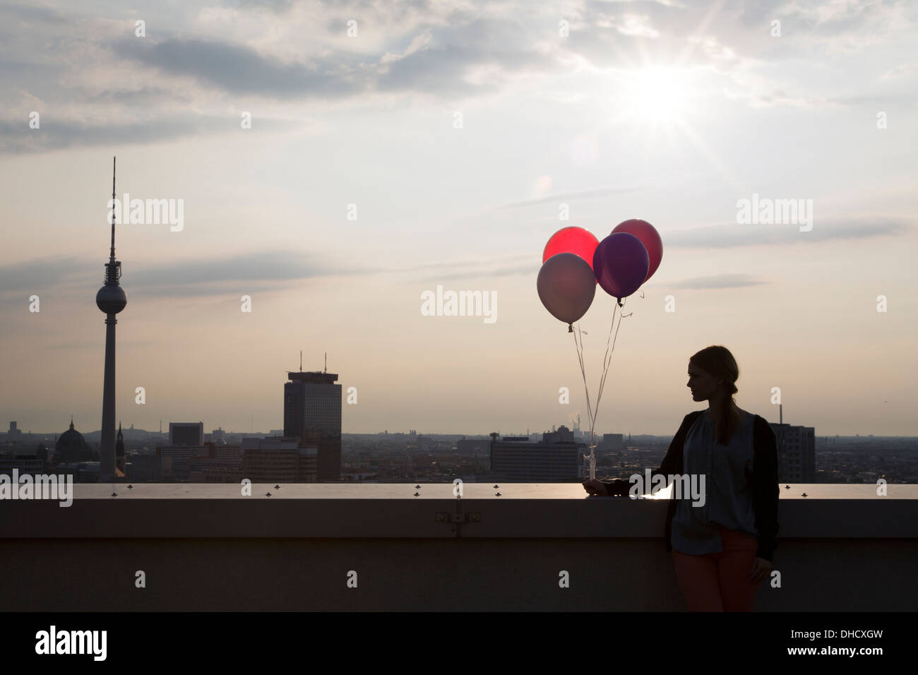Germany, Berlin, Young woman on rooftop terrace, holding balloons - Stock Image