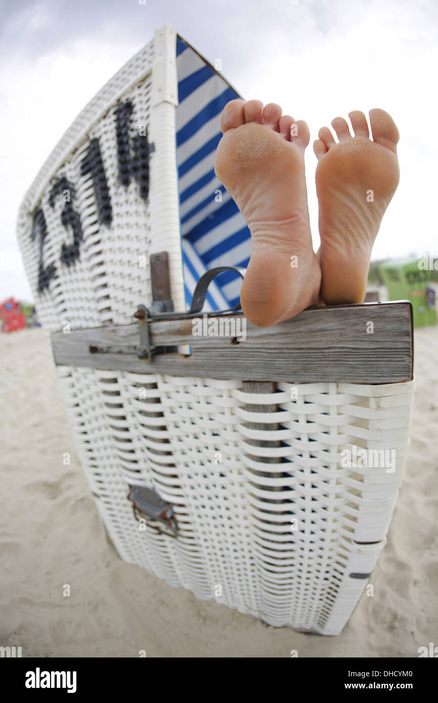 Germany, Lower Saxony, East Frisia, Langeoog, feet on an armrest of a roofed wicker beach chair - Stock Image