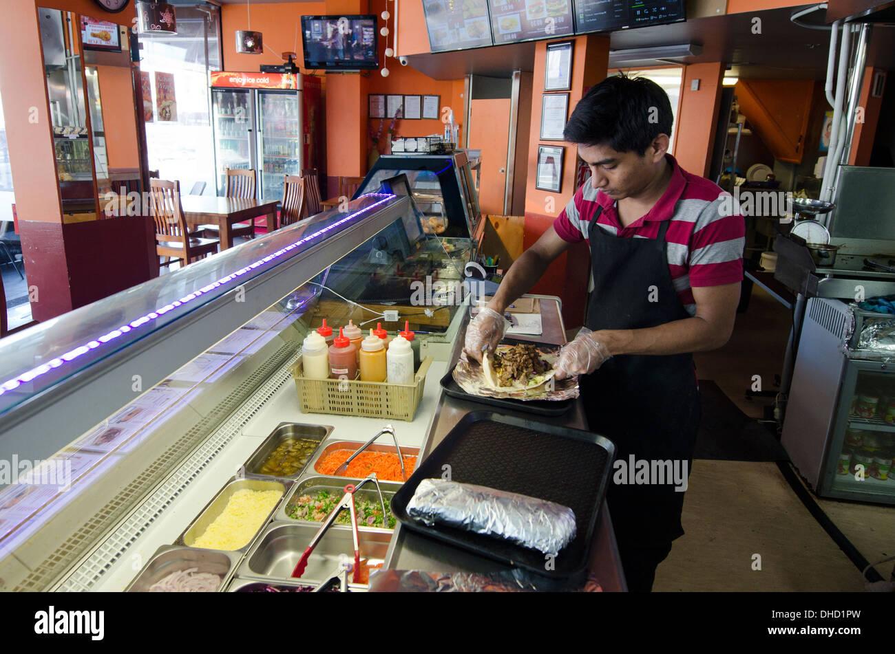 A man prepares a doner kebab or arab shawarma at a fast food restaurant - Stock Image