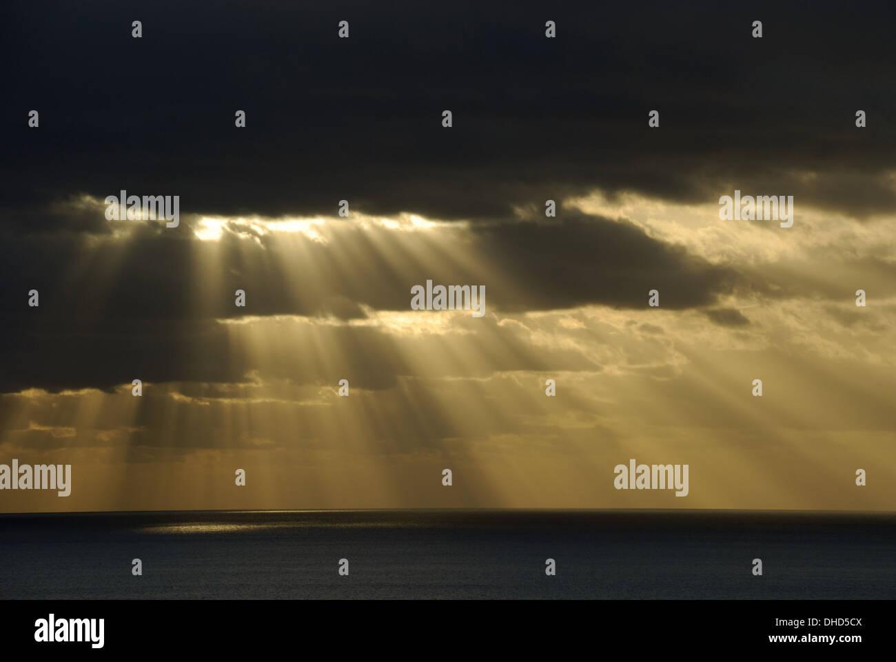 Sun shines through dark clouds - Stock Image